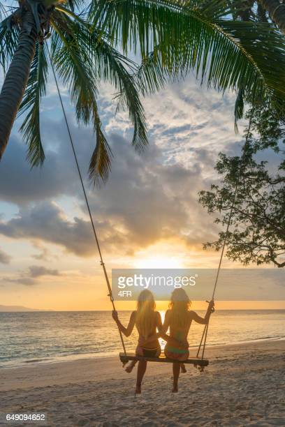 Two Women on a Swing in Bikini watching the Sunset