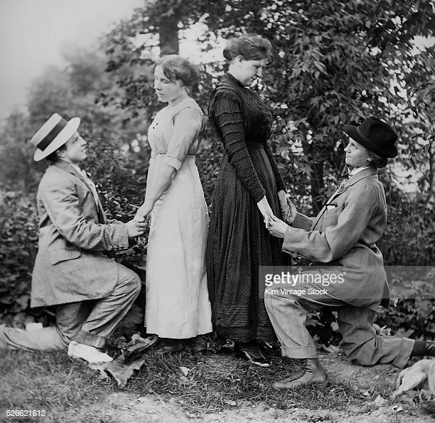 Two women on bended knee and dressed as men, appear to be proposing marriage to two women in unison, circa 1910.