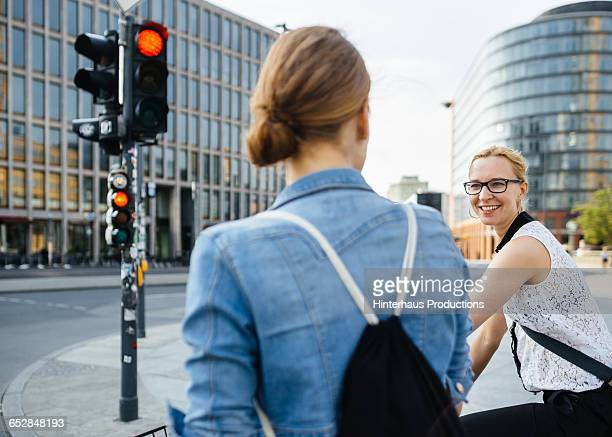Two women on bicycle waiting on traffic light