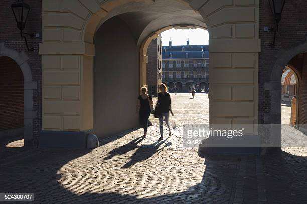 two women on binnenhof in the hague - binnenhof stock photos and pictures