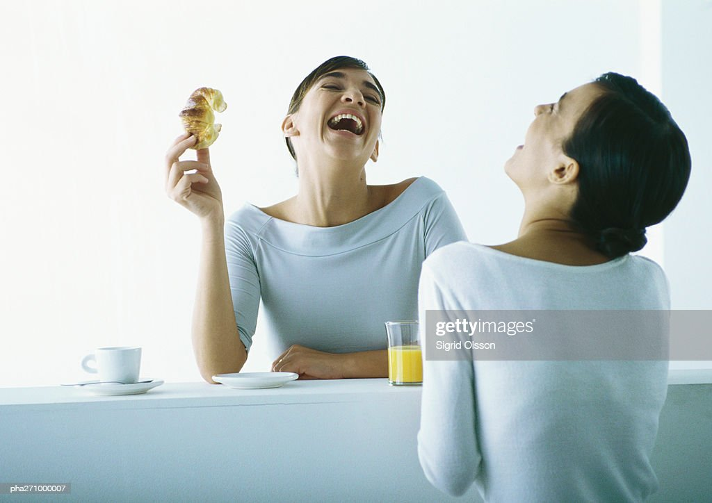 Two women on either side of bar having breakfast, laughing : Stockfoto