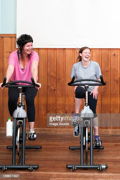 Two women on exercise bikes