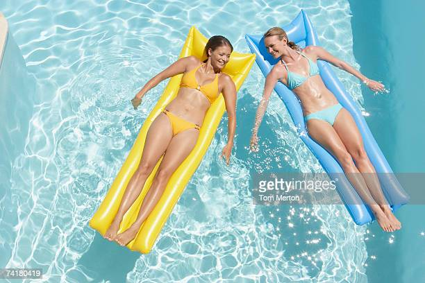 two women on flotation devices in pool - women sunbathing stock photos and pictures