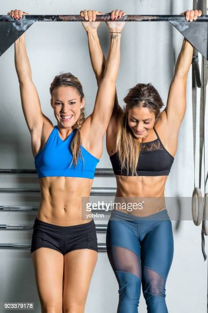 two women on gymnastic bar - chin ups stock photos and pictures