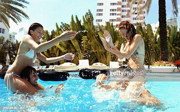 Two women on men's shoulders in swimming pool play fighting, side view