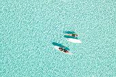 Two Women on Paddle Board in Blue Ocean