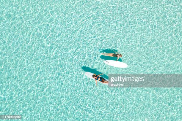 two women on paddle board in blue ocean - paddleboard stock photos and pictures