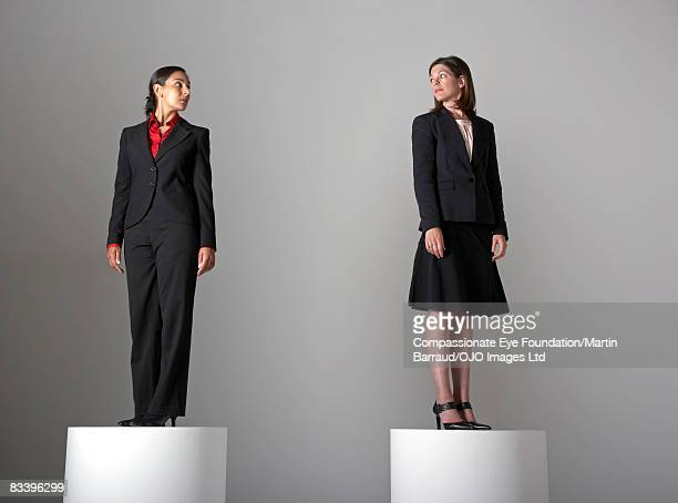 Two women on pedestals, looking at each other