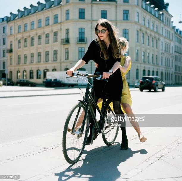 two women on same bike - only young women stock pictures, royalty-free photos & images