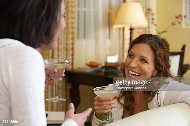 Two women on sofa laughing over cocktails
