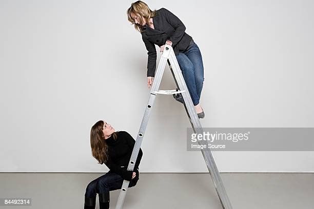 two women on step ladder - step ladder stock pictures, royalty-free photos & images