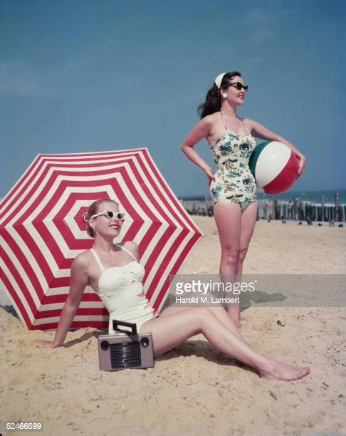Two women, both wearing sungalsses, pose on the beach, 1948. One, in a white bathing suit, sits on the sand in front of a red and white umbrella,...