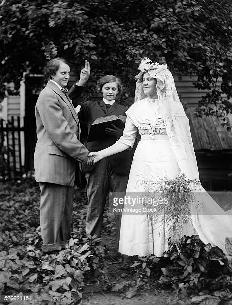 Two women, one dressed as a man, appear to be being married by a woman clergyperson.