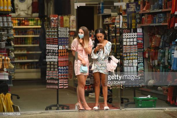 Two women, one wearing a face mask, stand in the doorway of a souvenir shop sheltering from the rain in Manchester, northwest England, on July 4 as...