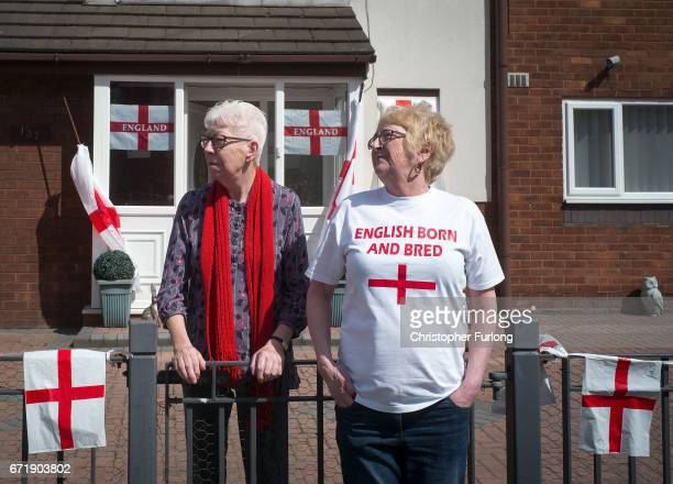Two women one wearing an 'English Born and Bred' tshirt watch the Manchester St George's Day parade through the streets on April 23 2017 in...