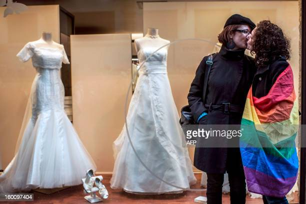 Two women one wrapped in a rainbow flag kiss in front of a wedding shop during a demonstration to support gay marriage and adoption on January 26...