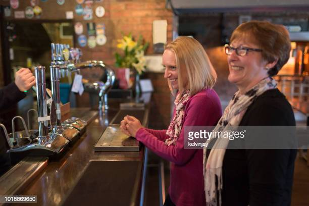 Two women ordering drinks in a restaurant bar