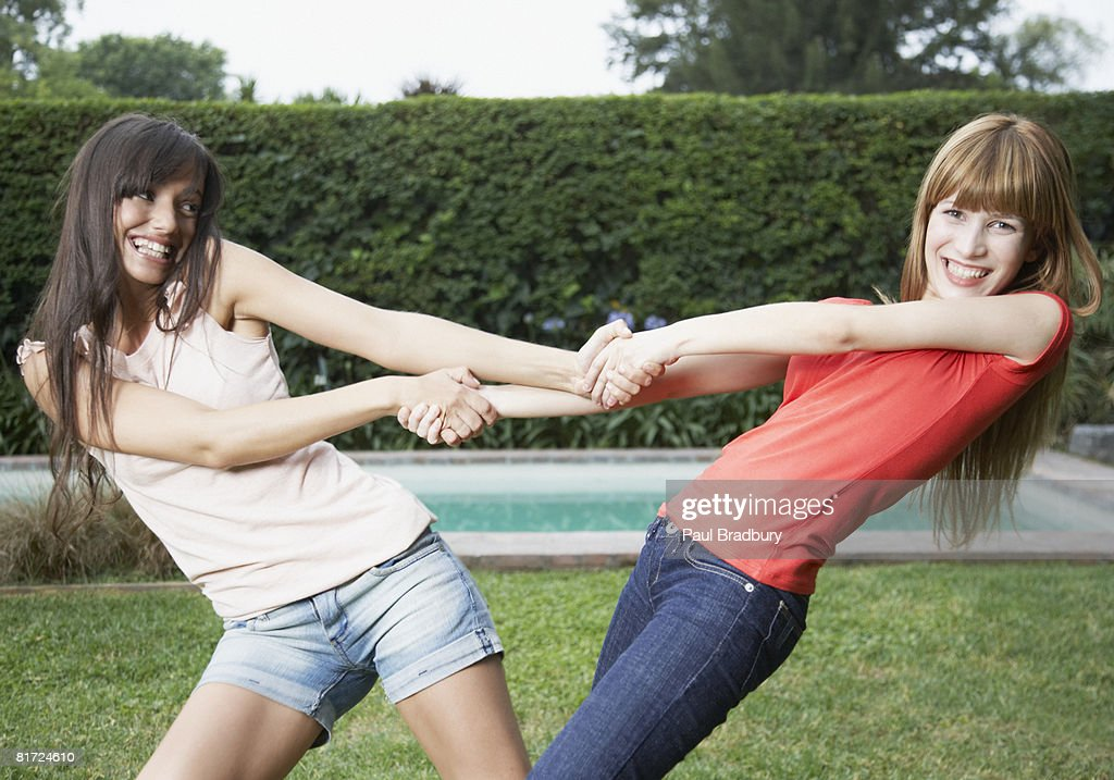 Two women outdoors pulling each others arms and smiling : Stock Photo