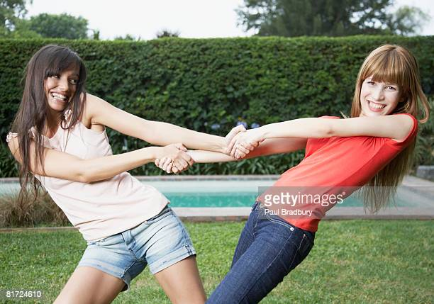two women outdoors pulling each others arms and smiling - female wrestling holds stockfoto's en -beelden