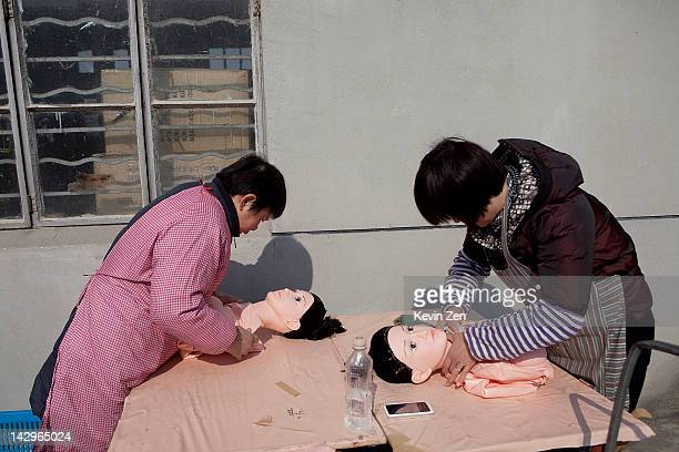 Two women pack finished sex dolls at the Jiamei Plastic Toy Factory on February 19 2012 in Ningbo China The Jiamei plastic toy company based in the...