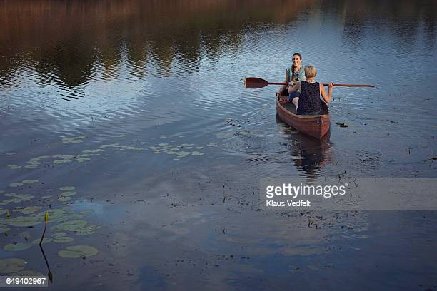 Two women paddling with canoe in lake