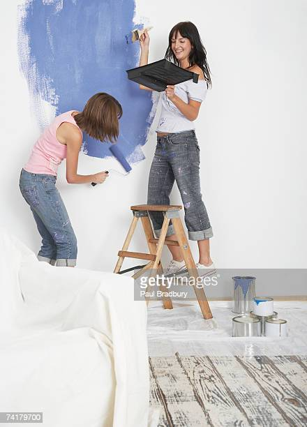 Two women painting room with thought balloon