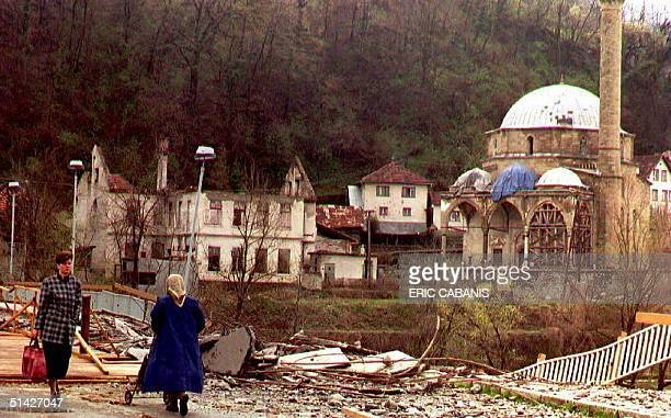 Two women pass a bridge damaged by Serb artillery fire to cross the Bosna river 27 March 1994 At right the halfdestroyed mosque of Maglaj The siege...