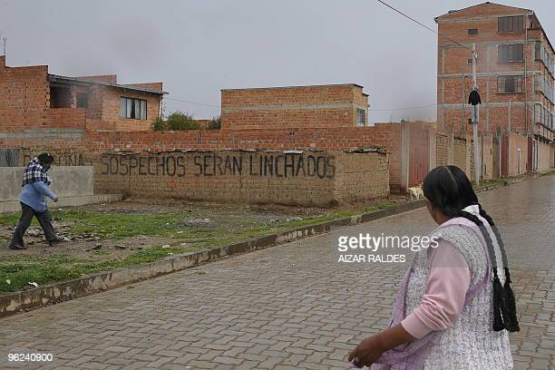 Two women pass by a graffiti on a wall that reads Suspects Shall Be LynchedJanuary 14 2010 at El Alto 10 km from La Paz According to unofficial...