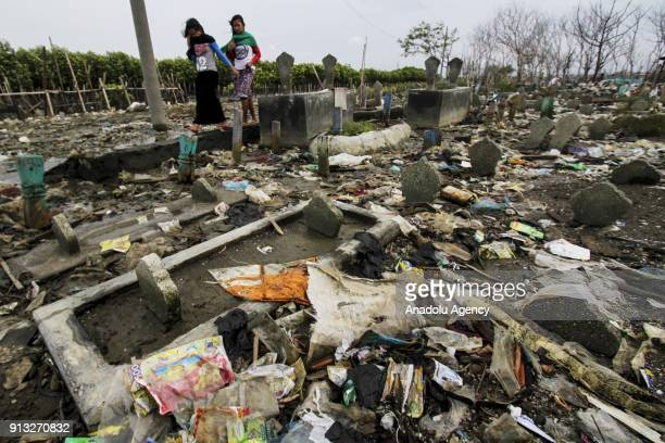 Two women pass by graves which are inundated by trash following the rising of sea level in Tambak Lorok village of Semarang Central Java Indonesia on...