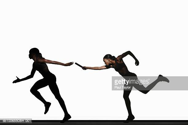 Two women passing relay baton