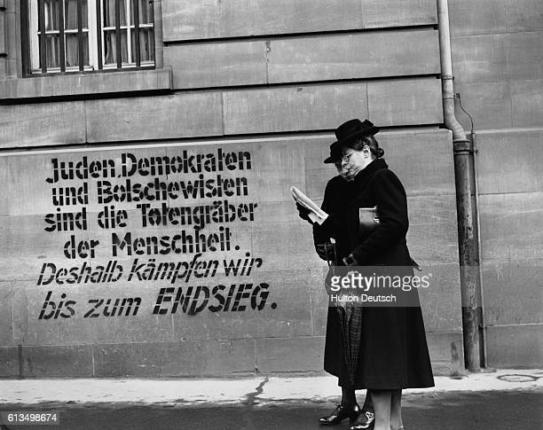 Two women pause beside profascist graffiti daubed on the wall of the Reichbank in Strasbourg to read the first French newspaper they have seen since...