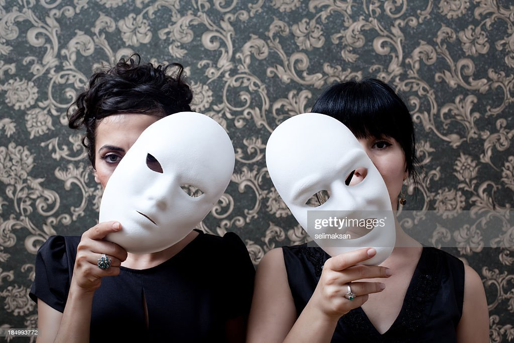 Two women peeking behind mask on wallpaper background : Stock Photo