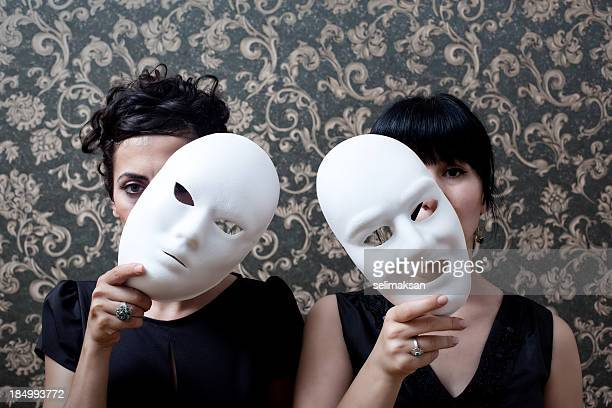 Two women peeking behind mask on wallpaper background