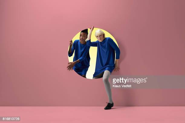 Two women peeking out of round opening in coloured wall
