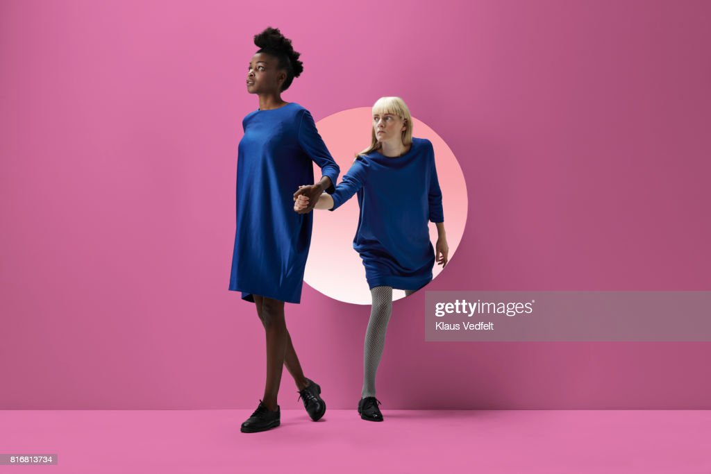 Two women peeking out of round opening in coloured wall : Stock Photo