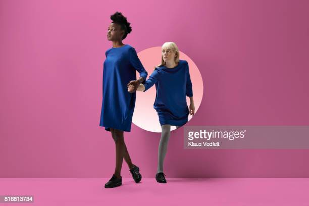 two women peeking out of round opening in coloured wall - caucasian appearance stock pictures, royalty-free photos & images