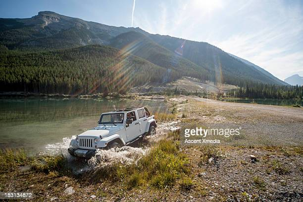 Two women pilot Jeep through lake shallows, mtns
