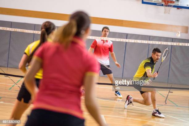 two women playing badminton against two men - badminton imagens e fotografias de stock
