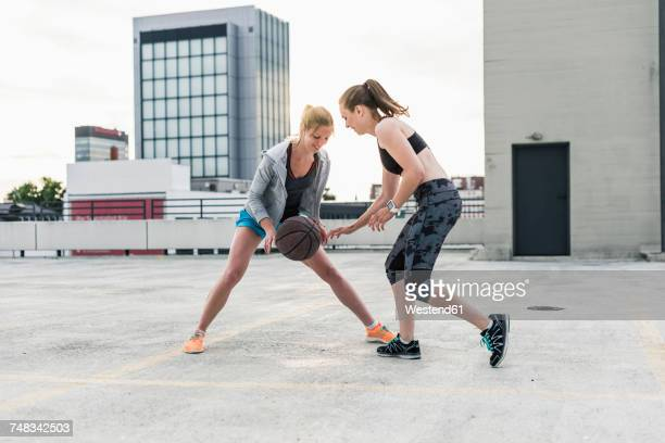 two women playing basketball on parking level in the city - driblar deportes fotografías e imágenes de stock