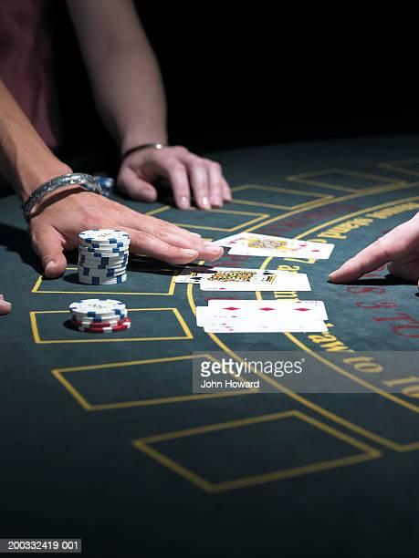 Two women playing Blackjack at gaming table, close-up