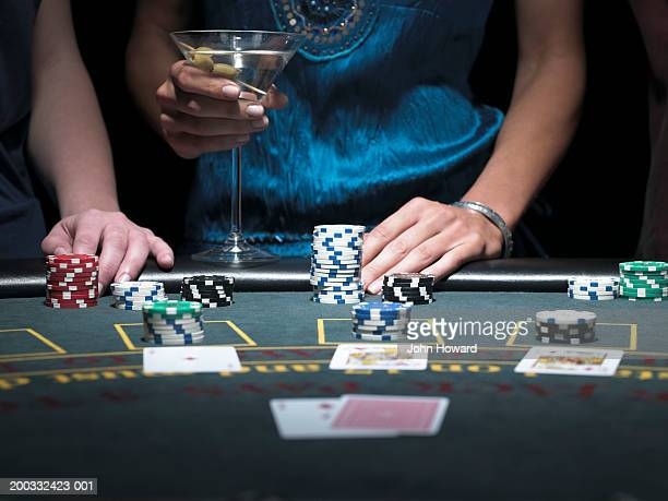 Two women playing Blackjack at gaming table, mid section