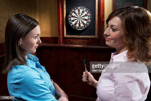 Two women playing darts in pub
