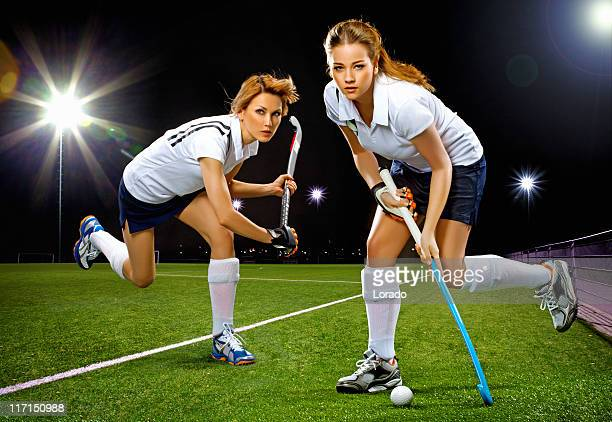 two women playing field hockey