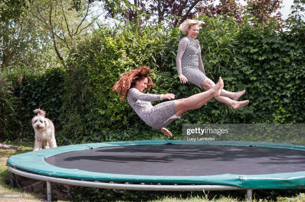 Two women playing on trampoline : Stock Photo