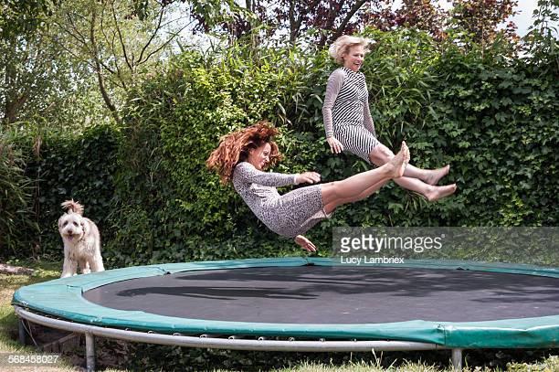 two women playing on trampoline - jung geblieben stock-fotos und bilder