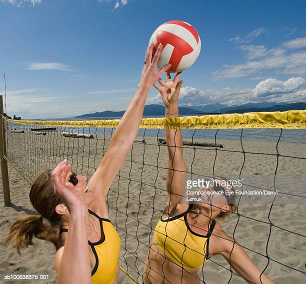 Two women playing volleyball on beach