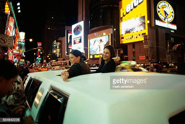 Two women poke through the sunroof of a limousine during a trip through Times Square