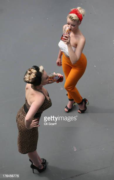 Two women pose as they drink real ale at the Great British Beer Festival in the Olympia exhibition centre on August 13 2013 in London England The...