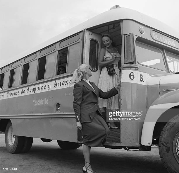 Two women pose as they exit the local bus in Acapulco Mexico
