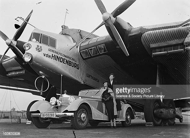 Two women pose beside Mercedes Benz car in front of plane by Zoltan Glass Two women pose beside Mercedes Benz car in front of plane Photograph taken...